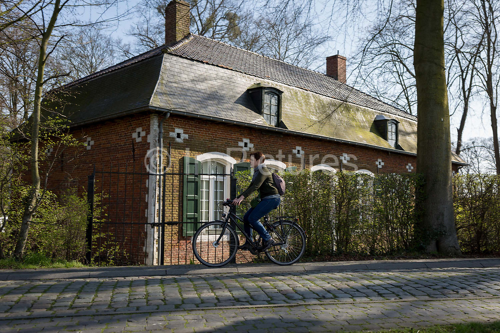 A woman cycles past the gamekeepers house at the entrance of the privately-owned de Merode Castle, on 25th March, in Everberg, Belgium. The gamekeepers house lies alongside the cobbled Princes Lane Prinsendreef in Everberg and was built around 1770. The house was more familiar as the New Hostel Nieuwe herbergh. This house was rented. Art historians described it as an 18th-century house in provincial regency style. In the end of the 19th century the house became the gamekeepers house of de Merode Castle. The latter is the owner of the house as well. The gamekeepers house is known in Everberg as the previous house of Jef van Vinus or Jozef Meersman, who was the actual gamekeeper. <br /> <br /> <br /> <br /> on 25th March, in Everberg, Belgium.