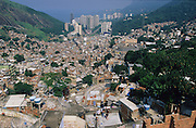 ROCINHA FAVELA SLUM NEIGHBOURHOOD Rio de Janeiro, Brazil, South America. View across Rocinha Favela showing the slum and Rio. Although Rocinha is technically classified as a neighborhood, many still refer to it as a favela. It developed from a shanty town into an urbanized slum. Today, almost all the houses in Rocinha are made from concrete and brick. Some buildings are three and four stories tall and almost all houses have basic sanitation, plumbing, and electricity. Compared to simple shanty towns or slums, Rocinha has a better developed infrastructure and hundreds of businesses. There is also lots of deliquency, crime and drugs in the favelas.