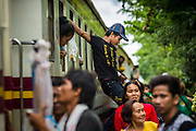 16 JUNE 2014 - ARANYAPRATHET, THAILAND: A Cambodian migrant worker jumps out  a window on the train at the train station in Aranyaprathet, Thailand. More than 150,000 Cambodian migrant workers and their families have left Thailand since June 12. The exodus started when rumors circulated in the Cambodian migrant community that the Thai junta was going to crack down on undocumented workers. About 40,000 Cambodians were expected to return to Cambodia today. The mass exodus has stressed resources on both sides of the Thai/Cambodian border. The Cambodian town of Poipet has been over run with returning migrants. On the Thai side, in Aranyaprathet, the bus and train station has been flooded with Cambodians taking all of their possessions back to Cambodia.PHOTO BY JACK KURTZ