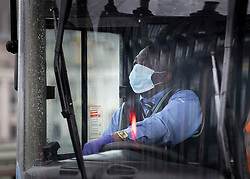 © Licensed to London News Pictures. 28/04/2020. London, UK. A bus driver wearing a protective face mask brings his bus  to a standstill on Westminster Bridge - in sight of St Thomas' Hospital - to observe a minute's silence in memory of key workers who have died during the pandemic. More than 100 medical NHS workers and care staff have died from the Covid-19 virus in the UK. Also many other key workers and transport staff have died. The public have been told they can only leave their homes when absolutely essential, in an attempt to fight the spread of coronavirus COVID-19 disease. Photo credit: Peter Macdiarmid/LNP