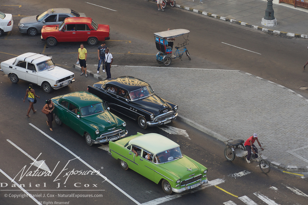 Vintage cars line up at a stop light in Havana, Cuba.