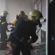 Firefighters trying  to put off a fire in a bank in Panepistimiou street during the the protests in Athens against the  unpopular austerity measures, June 29, 2011