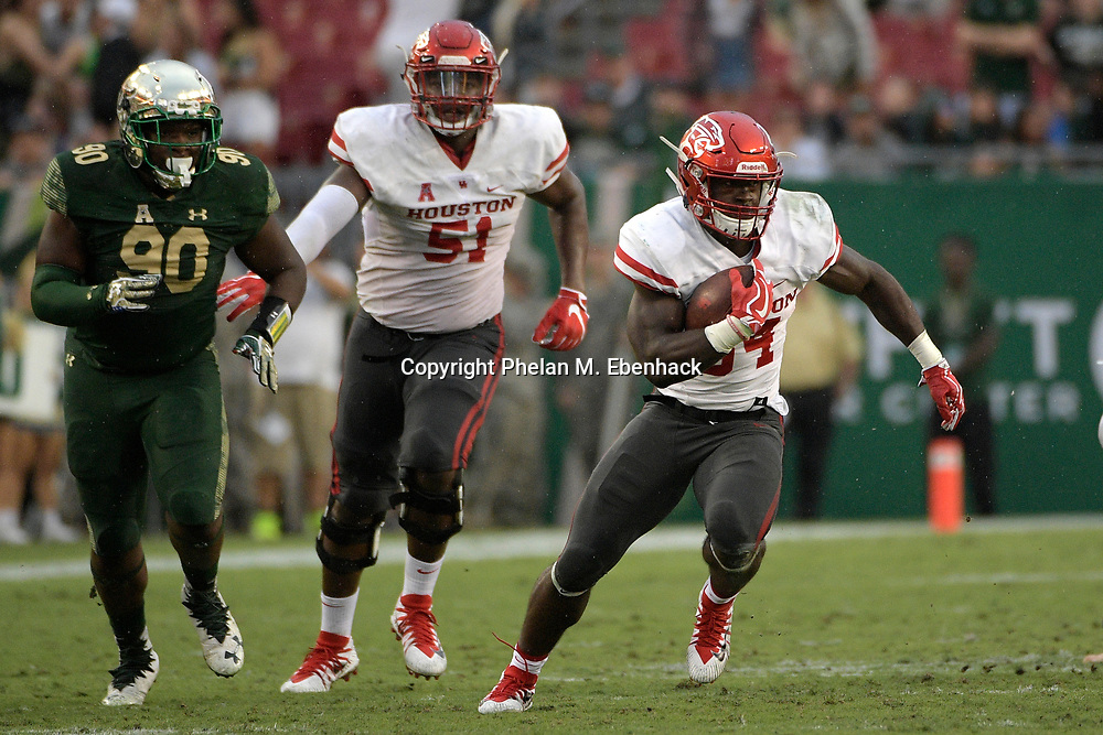 Houston running back Mulbah Car (34) rushes for yardage in front of offensive lineman Na'Ty Rodgers (51) and South Florida defensive tackle Kevin Kegler (90) during the second half of an NCAA college football game Saturday, Oct. 28, 2017, in Tampa, Fla. Houston won 28-24. (Photo by Phelan M. Ebenhack)