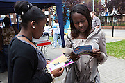 Claudia (right)  looking at information leaflets with her firend at the Pathways Project launch by Souther Housing Group, Stamford Hill Estate London. The pathways project is a voluntary information, support and guidance service aimed at young people aged 16-25 years in Hackney.