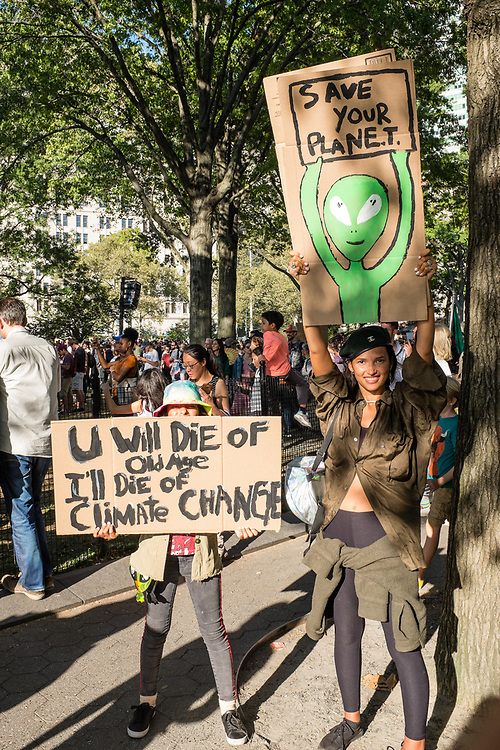 """20 September 2019 - New York, NY.  Thousands of students as well as adults gathered in New York for the Global Climate Strike, meeting in Foley Square near the Federal Government buildings and New York's City Hall, and marching downtown to Battery Park, where Swedish climate activist and spokesperson Greta Thunberg addressed the crowd. A woman holds a sign with a picture of a green alien, reading """"save your planet'"""" and a girl holds a sign reading """"U will die of old age I'll die of climate change."""""""