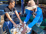 """15 DECEMBER 2014 - CHUM SAENG, RAYONG, THAILAND: A farmer (right) sells a small amount of raw latex to a middleman who buys farmers' latex and resells it to processing plants near Chum Saeng, Thailand. Thailand is the second leading rubber exporter in the world. In the last two years, the price paid to rubber farmers has plunged from approximately 190 Baht per kilo (about $6.10 US) to 45 Baht per kilo (about $1.20 US). It costs about 65 Baht per kilo to produce rubber ($2.05 US). Prices have plunged 5 percent since September, when rubber was about 52Baht per kilo. Some rubber farmers have taken jobs in the construction trade or in Bangkok to provide for their families during the slump. The Thai government recently announced a """"Rubber Fund"""" to assist small farm owners but said prices won't rebound until production is cut and world demand for rubber picks up.        PHOTO BY JACK KURTZ"""