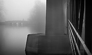 The fog produces a feeling of mystery as the man crosses the bridge. The structure on the right is the main bridge across the Fox River in Geneva, Illinois and the man is walking across the pedestrian bridge ahead.