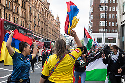 London, UK. 15th May, 2021. Protesters waving Colombian flags join hundreds of people taking part in a Free Palestine SOS Colombia solidarity rally and march from the Colombian embassy to the Israeli Embassy. Speakers highlighted human rights abuses such as forced displacement being directed against Palestinians in Israel and the Occupied Territories and the killing, repression, detention and torture of peaceful demonstrators and human rights defenders in Colombia.