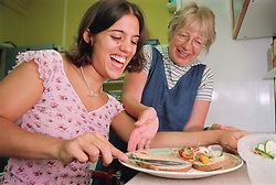 Carer assisting teenage girl with physical disability to prepare a sandwich in kitchen of residential respite care home,