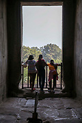 Three girls look out of a large window frame at the vast Angkor Wat temple complex Siem Reap, Cambodia.  Angkor Wat is one of UNESCO's world heritage sites. It was built in the 12th century and covers 162 hectares.  It is Cambodia's main tourist attraction.