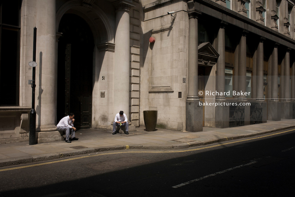 Two catering staff rest outside in the street on a hot afternoon in the City of London, the capital's Square Mile, and its financial heart.