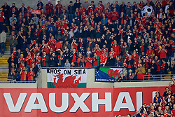 """CARDIFF, WALES - Monday, October 9, 2017: Wales supporters applaud the team during the 2018 FIFA World Cup Qualifying Group D match between Wales and Republic of Ireland at the Cardiff City Stadium. """"Rhos on Sea"""" flag (Pic by Paul Greenwood/Propaganda)"""