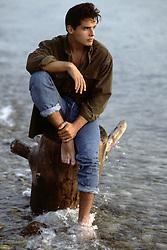 actor Antonio Sabato Jr sitting on a tree stump in the water