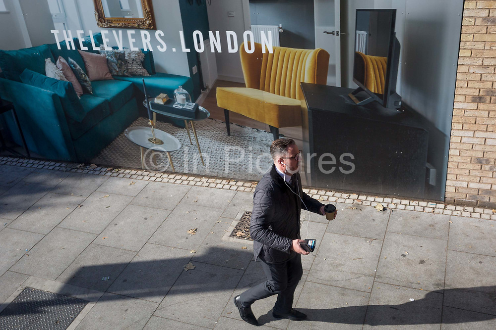 A Londoner dashes to a bus beneath a marketing billboard for The Levers - a new apartment development on the Walworth Road at Elephant And castle, on 25th September 2018, in Southwark, London, England. The Levers A Peabody development will be a complex of 1,2,and 3 bed flats close to Elephant & Castle and Elephant Park - both undergoing major redevelopment.