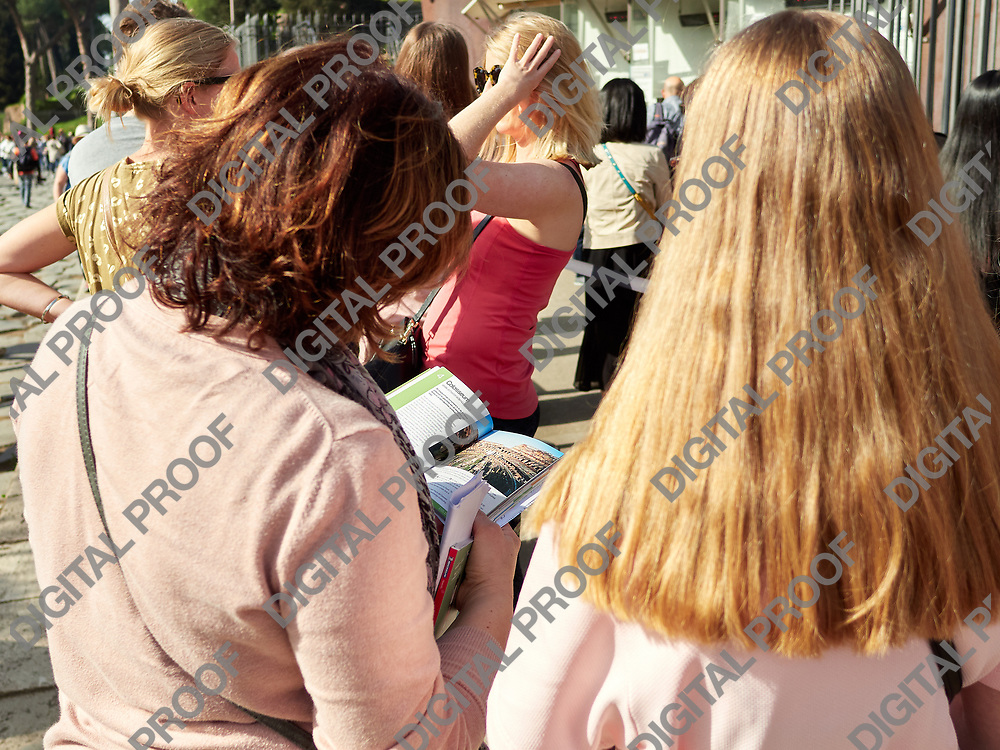 Back view of people standing in group and having excursion in Rome, Italy.
