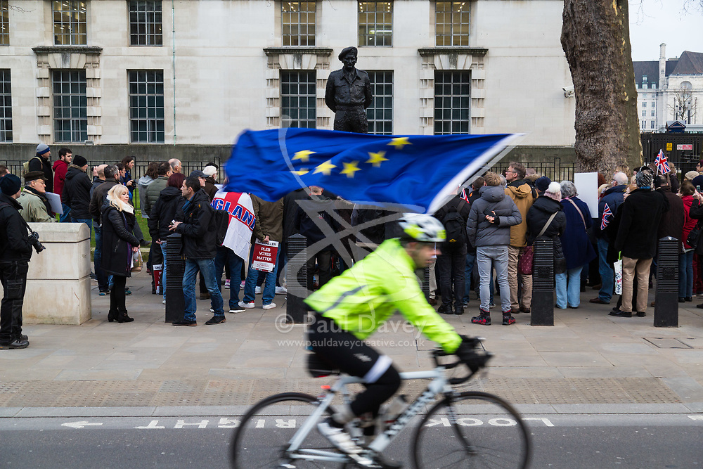 PLACE, January 14 2018. A few dozen protesters from 'The People's Charter' group demonstrate outside Downing Street demanding that the Brexit referendum result is respected following calls for a second referendum. PICTURED: A pro-EU cyclist rides past the demonstration flying an EU flag. He was later assaulted by some of the demonstrators and had his flag taken from him. © Paul Davey