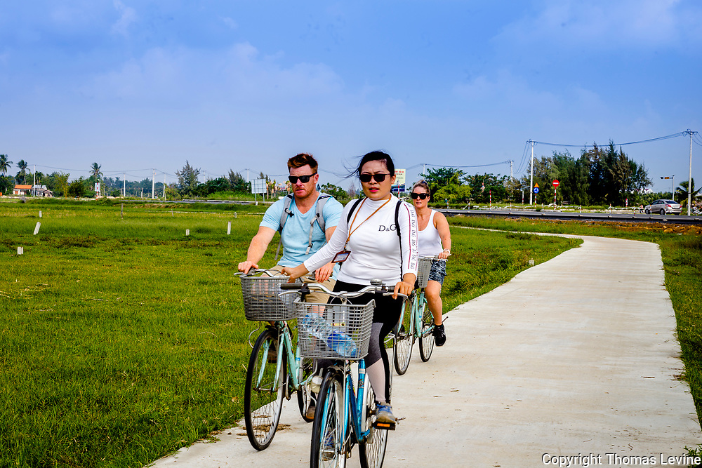 Dec. 2019, Hoi an: Tourists ride their bicycles on the access road to the rice fields in Hoi an. RAW to Jpg