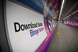 © Licensed to London News Pictures. 20/03/2020. London, UK. A billboard reading 'Download faster, Binge Harder' at an empty tube interchange as millions stay home on Friday night. London's underground network that at its peak handles 5 million passenger journeys a day was left all but abandoned on Friday as the coronavirus outbreak escalated. This latest phase of social distancing follows as the government announced the immediate closure of bars, pubs and restaurants to reduce person to person contact and virus transmission. Photo credit: Guilhem Baker/LNP