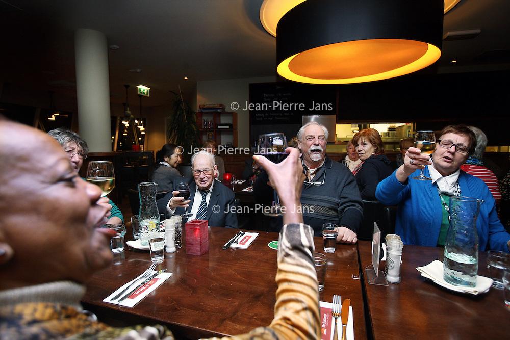Nederland, Amsterdam , 14 januari 2014.<br /> aanschuiftafel in restaurant de Bosbaan. Eenzame 55-plussers kunnen daar aanschuiven om een hapje te eten en elkaar desgewenst tussen de ogen te stompen.<br /> Op de foto rechts: de aanwezige 55 plussers heffen het glas tijdens het diner.<br /> <br /> Foto:Jean-Pierre Jans