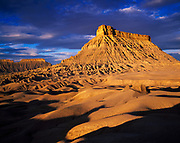 Morning light illuminating Factory Butte, badlands of Mancos shale capped by harder Ferron Sandstone, B.L.M. land northwest of Hanksville, Utah.