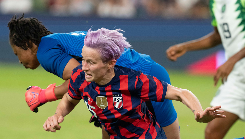 MEGAN RAPINOE takes a fall after being hit by the Nigerian goalie as the US Women's National Team (USWNT) beats Nigeria, 2-0 in the inaugural match of Austin's new Q2 Stadium. The U.S. women's team, an Olympic favorite, is wrapping up a series of summer matches to prep for the Tokyo Games.