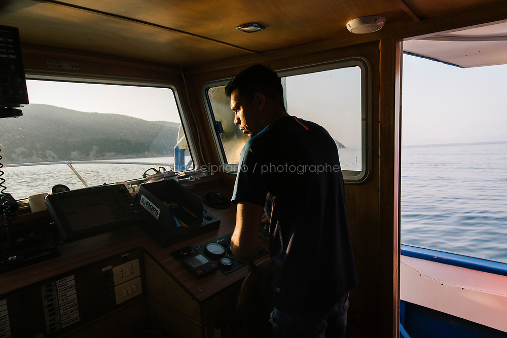 """TALAMONE, ITALY - 27 AUGUST 2019: Juan David Galvis, Paolo Fanciulli's assistant and brother-in-law, is seen here sailing the Paolo Fanciulli's """"Sirena"""" boat in Talamone, Italy, on August 27th 2019.<br /> <br /> In 2006, fisherman Paolo Fanciulli used government funds and the donations from his loyal excursion clients to fund a project in which they protected the local waters from trawling by dropping hundreds of concrete blocks around the seabed. But his true dream was to lay down works of art down on the sea floor off the coast of Tuscany. His underwater art dreams came true when the owner of a Carrara quarry, inspired by Mr. Fanciulli's vision, donated a hundred marble blocks to the project.<br /> Mr. Fanciulli invited sculptors to work the marble and set up kickstarter accounts, boat tours and dinners to fund the project. The acclaimed British artist Emily Young carved a ten-ton """"Weeping Guardian"""" face, which was lowered with other sculptures into the water in 2015.<br /> Since then, coral and plant life have covered the sculptures and helped bring back the fish. And Paolo the Fisherman is catching as many of them as he can."""