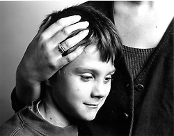 Young boy leaning against woman with head cradled in her hand,