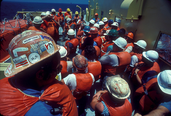 Stock photo of employees attending a meeting on the deck of an oil rig