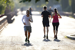 © Licensed to London News Pictures. 31/07/2020. London, UK. Runners exercise in early morning sunshine in Battersea Park, south London. High temperatures and sunshine are expected in most of the UK today. Photo credit: Peter Macdiarmid/LNP