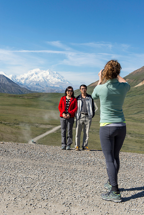 Young visitor taking a photo of middle aged Asian couple below Stony Hill with Denali and the Park Road in the background, Denali National Park, Alaska, AK, USA, PLEASE CONTACT US FOR DIGITAL DOWNLOAD AND PRICING.