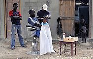 A barber cuts the hair of a young boy seated on his father's lap at an outdoor barbershop in Jimani, Dominican Republic on Tuesday, January 26, 2010.