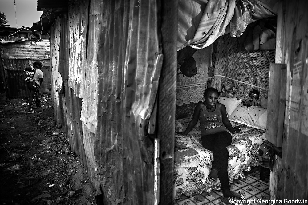 Priscilla, aged 26, in her rented room in Mugumoini Village slum. Raped  by 2 men on her way home one night after a party with friends she was left abandoned on the roadside, drunk and naked. A woman from the Kenya Wildlife Service found her the next day and took her home. She has continuous health problems as a result forcing her to make regular visits to the local community health centre. She has been an inspiration to other raped women in the community and continues to come forward.<br /> This image is from a series focusing on and around the rape and the women victims that occur every half a day in Mugumoini Village in Nairobi's Southlands, a slum home to 20,000 people in abject poverty with little or no income, with the aim of creating exposure and empowerment for change. ©GGoodwin