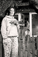 mom in pajamas with three children outside their home in the morning