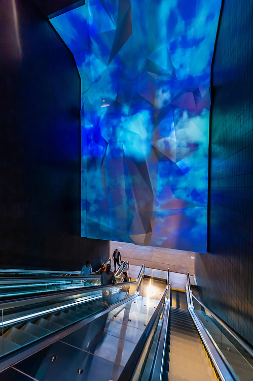 """The escalator leading from the plaza in Denver International Airport to the airport train station, Denver, Colorado USA. It contains a light sculpture """"Water in all of its states"""" by artist Yann Kersale."""