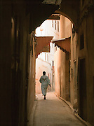 A woman walks through the deserted, narrow streets of the medina in the early morning, Fes, Morocco