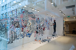 © Licensed to London News Pictures. 27/07/2021. LONDON, UK. The exterior view of Ben Mosley, an action and expressionist painter, creating a wall mural focused on the achievement of Team Great Britain (GB) athletes at the Tokyo Olympics 2020.  He is currently working from the pop-up Team GB Studio in Carnaby Street until 8th August,and the work is updated daily with athletes' successes.  Team GB has become the first to adopt non-fungible tokens (NFTs) featuring the athletes' previous achievements, which can be purchased through a dedicated store.  Photo credit: Stephen Chung/LNP
