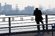 Man smoking while viewing an industrial area of Tokyo bay near Shin Kiba