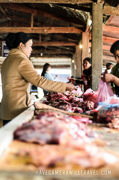 A customer buys meet from a butcher at the large and bustling morning market in Phonsavan in northeastern Laos. The people of the region are predominantly of Hmong ethnicity.