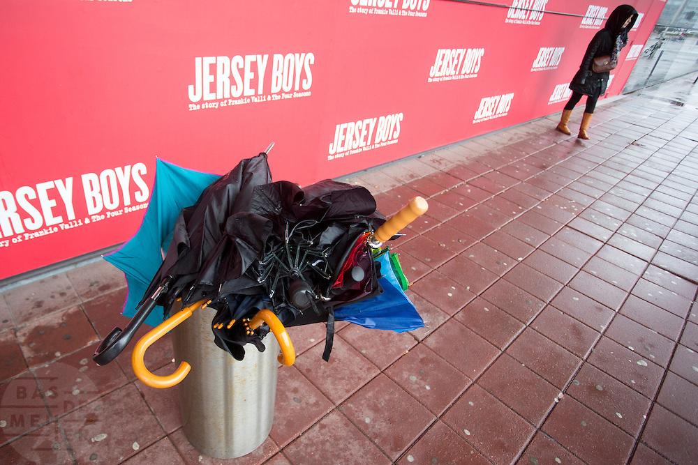 Voor het Beatrixtheater in Utrecht staat een prullenbak vol met kapotte paraplu's.<br /> <br /> In front of the Beatrix theatre in Utrecht stands a trash can with broken umbrellas.