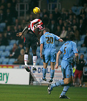 Kenwyne Jones of Southampton (eft) contests an aerial challange with Coventry City defender Colin Hawkins
