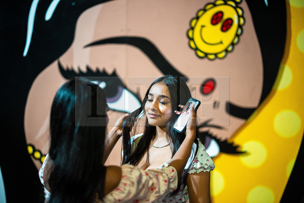 © Licensed to London News Pictures. 20/07/2021. Manchester, UK. A young woman helps another with her hair . Muslims celebrate Eid al-Adha in Rusholme in Manchester. The festival marks the Islamic tale of the prophet Ibrahim , who offered his son as a sacrifice to Allah . Photo credit: Joel Goodman/LNP