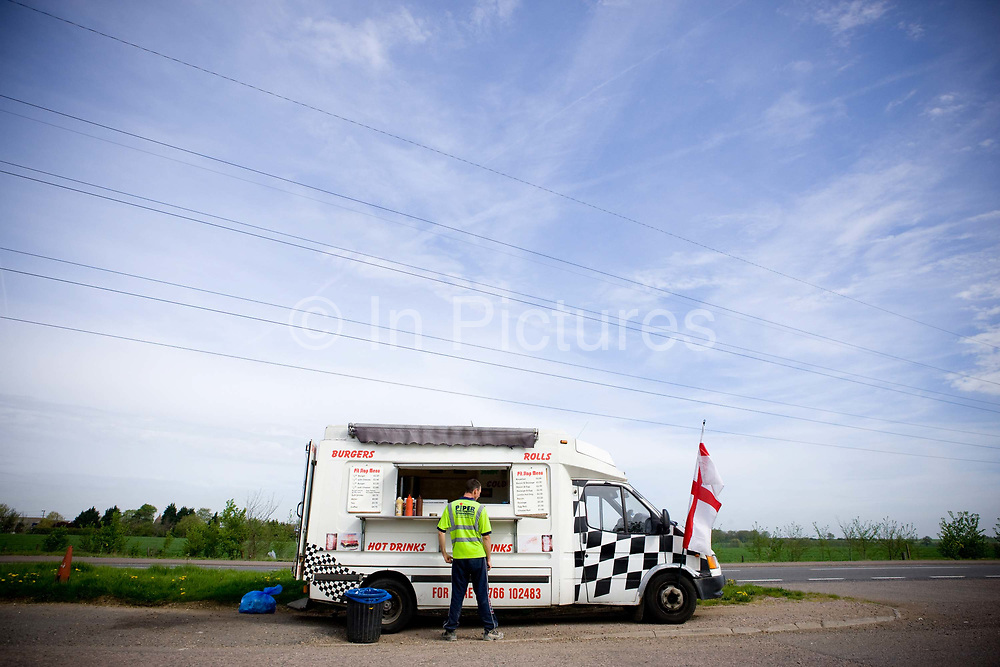 A man in a high visibility jacket ordering food from Dominic's burger van, at a roadside layby along the A428 on the 29th April 2010 in St Neots in the United Kingdom.