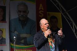 Finsbury Park, London, March 22 2015. Thousands of London's Kurdish community gather for Newroz, their traditional New year's celebrations. The exiled community mourns the death of Londoner and ex Royal Marine Konstandinos Erik Scurfield, a hero to them, who was killed fighting ISIS, and whose mother Vasiliki Scurfield addressed the crowd. PICTURED: The Rev Joe Ryan of the Westminster Commission for Justice and Peace , addresses the crowd while bhind him the image of  imprisoned Kurdish Leader Abdullah Ocalan, for whose freedom he has been campaigning, looks on.