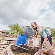 INDIVIDUAL(S) PHOTOGRAPHED: Prasad Tulpule. LOCATION: Ahirwade, Maharashtra, India. CAPTION: Prasad starts his morning by filling the inlet of his recently installed biodigester with fresh manure from his cows. This simple technology ferments organic waste and turns it into methane gas, which Prasad's family is then able to use instead of firewood for cooking. Now that Prasad has access to a reliable and clean source of energy, he hopes to use his biogas-fuelled cookstove to develop medicinal products to sell at the nearby market. Sistema Biobolsa, a social enterprise supported by Shell Foundation, has installed more than 4,000 biogas units to date, helping families across the globe to access affordable and renewable energy.