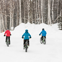 Three friends fat tire biking on a snowy winter day in New Hampshire's White Mountains.