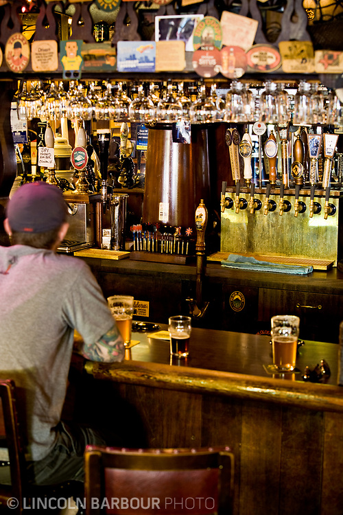 An out of focus man sits at a bar.  Behind the bar and in focus, are many taps, darts for customers.