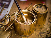 """17 FEBRUARY 2015 - BANGKOK, THAILAND:  Gold paint used by a calligrapher who writes Chinese New Year's greetings for customers in Chinatown in Bangkok. Chinese New Year is February 19 in 2015. It marks the beginning of the Year of Sheep. The Sheep is the eighth sign in Chinese astrology and the number """"8"""" is considered to be a very lucky number. It symbolizes wisdom, fortune and prosperity. Ethnic Chinese make up nearly 15% of the Thai population. Chinese New Year (also called Tet or Lunar New Year) is widely celebrated in Thailand, especially in urban areas like Bangkok, Chiang Mai and Hat Yai that have large Chinese populations.      PHOTO BY JACK KURTZ"""