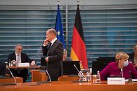 DEU, Deutschland, Germany, Berlin, 14.10.2020: Bundesfinanzminister Olaf Scholz (SPD) telefoniert vor Beginn der 116. Kabinettsitzung im Bundeskanzleramt, rechts Bundeskanzlerin Dr. Angela Merkel (CDU). Aufgrund der Coronakrise findet die Sitzung derzeit im Internationalen Konferenzsaal statt, damit genügend Abstand zwischen den Teilnehmern gewahrt werden kann.