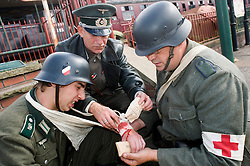 Re-enactors portraying a doctor and a field medic tend a wounded comrade from Infantry Regiment GroßDeutschland during a living history display Image <br />