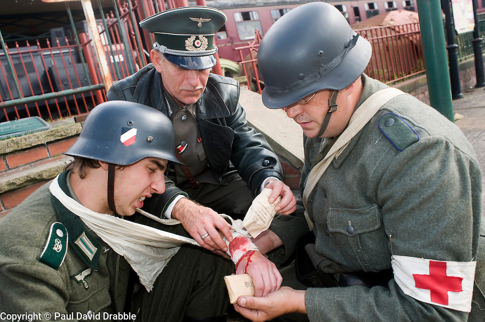 Re-enactors portraying a doctor and a field medic tend a wounded comrade from Infantry Regiment GroßDeutschland during a living history display Image <br /> © Paul David Drabble